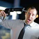 Businessman putting gas nozzle to his head, screaming.